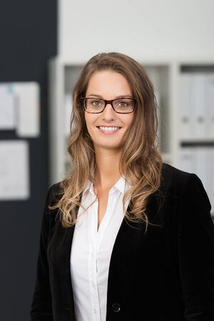 company person: Close up Smiling Young Businesswoman, in Black Coat and Eyeglasses, with Long Blond Hair, Looking at the Camera Inside the Office.