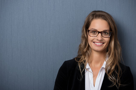 Close up Happy Young Businesswoman with Blond Hair on Gray Background with Copy Space on Left Side While Looking at the Camera. Stockfoto