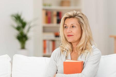 mujer pensativa: Pensativo atractiva mujer de mediana edad que abraza un libro contra su pecho mientras se sienta en su pensamiento sal�n sobre lo que ha le�do