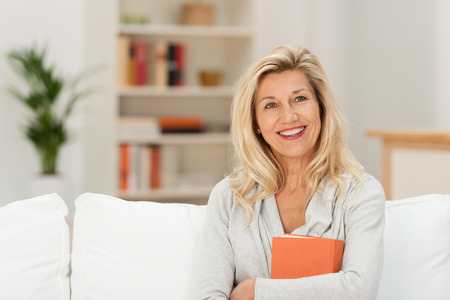 boomer: Attractive middle-aged woman with a lovely smile sitting on a sofa in the living room clutching a book Stock Photo