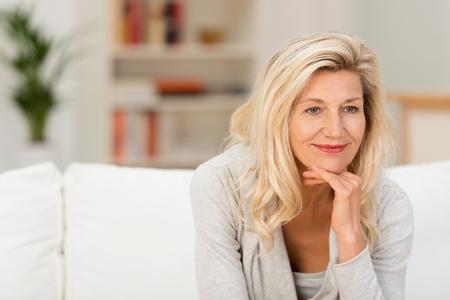 Sonriente mujer atractiva sentado pensando en un sofá en casa con la barbilla apoyada en la mano mirando a un lado de la cámara Foto de archivo - 34559667