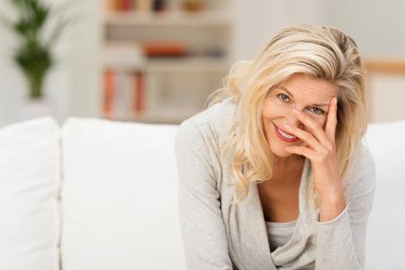 카메라를 그녀의 손가락을 통해 웃고 거실에서 소파에 앉아 즐겁게 매력적인 금발 여자