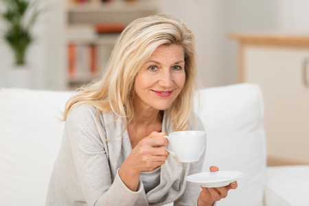 best coffee: Smiling woman relaxing with a cup of coffee or tea as she sits on a sofa at home taking a break