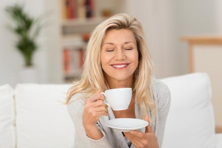 tomando café: Mujer de mediana edad saboreando su café sentado sosteniendo una taza y el plato en el sofá con los ojos cerrados y sonrientes sonrisa de felicidad