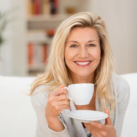 mujer tomando cafe: Feliz vivaz mujer rubia de mediana edad con una taza de té o café mirando a la cámara con una sonrisa cálida radiante