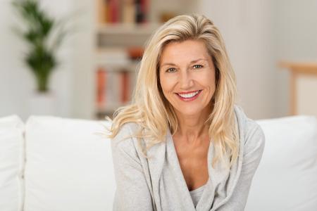Mooie middelbare leeftijd blonde vrouw met een stralende glimlach op een sofa zitten thuis te kijken naar de camera Stockfoto