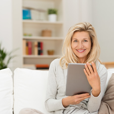 Smiling attractive middle-aged blond woman sitting on a couch at home holding a tablet-pc and looking at the camera Stock Photo