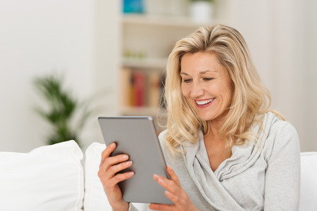 persons: Middle-aged woman reading a message, e-book or information on her tablet computer with a look of excited anticipation as she sits on a couch at home Stock Photo
