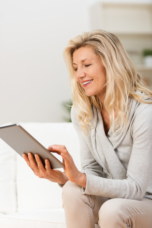 Happy blond middle-aged woman sitting on a sofa navigating the internet on a tablet with a smile Stock Photo