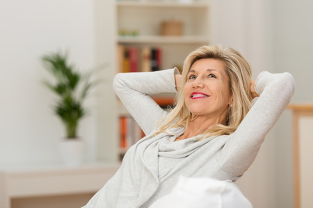 Woman relaxing at home with a contented smile as she leans back in her chair with her hands behind her head looking up into the air with a look of pleasure Stock Photo