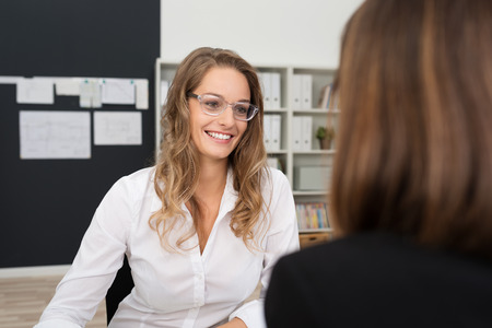 costumer: Happy Pretty Office Woman with Blond Hair, Wearing White Long Sleeve Shirt and Eyeglasses, Talking to Office-mate at her Worktable Area.