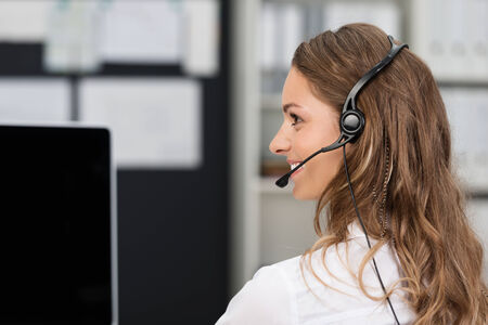 costumer: Young businesswoman in a call center or client services desk wearing a headset and smiling as she assists a customer Stock Photo