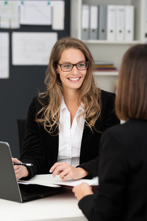 costumer: Pretty businesswoman having a discussion in the office with a female colleague, over the shoulder view of the lady in glasses
