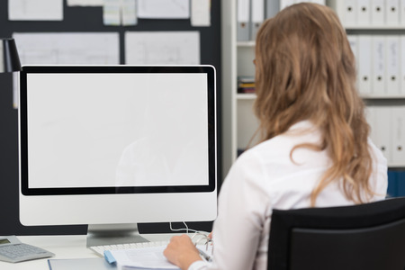 Businesswoman sitting with her back to the camera working at a desktop computer with the blank screen visible to the viewer Standard-Bild