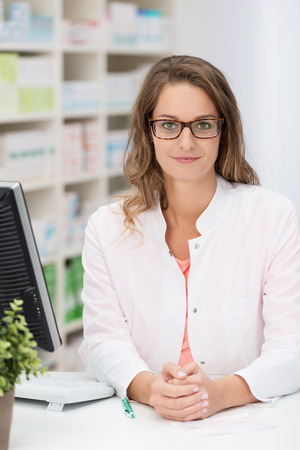 Confident female pharmacist wearing glasses standing behind the counter in the pharmacy looking at the camera photo