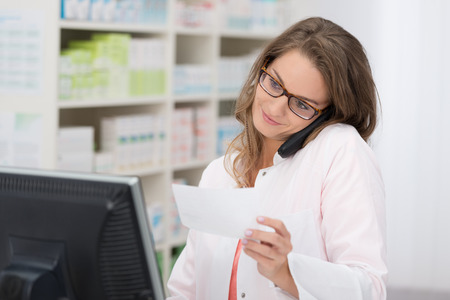 Pretty female pharmacist wearing glasses discussing a medical prescription she is holding with a customer on her phone Archivio Fotografico