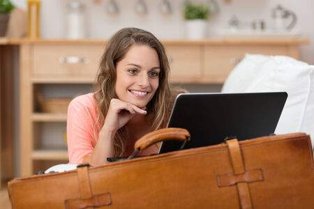 vacation home: Smiling young woman on vacation leaning on an old leather suitcase reading a tablet computer as she keeps in touch with friends and family Stock Photo