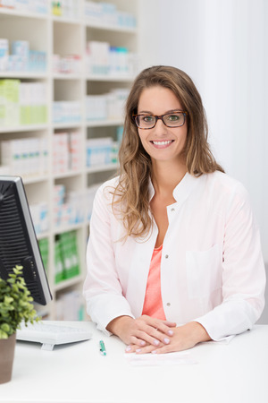 Pretty young female pharmacist standing behind her desk at the pharmacy smiling at the camera