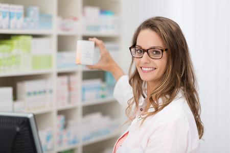 Sonriendo atractiva mujer farmacéutico joven promoción de un producto en una caja blanca en blanco que ella está sosteniendo en su mano en la farmacia Foto de archivo