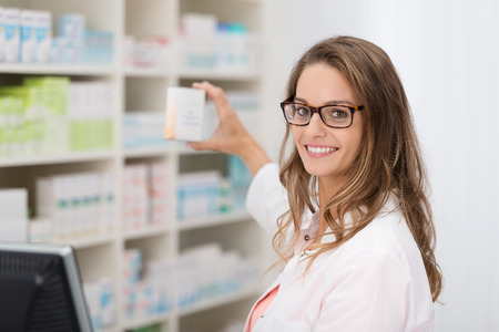Smiling attractive young female pharmacist promoting a product in a blank white box she is holding up in her hand in the pharmacy