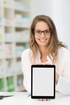 Smiling attractive young woman pharmacist wearing glasses standing behind the counter in the pharmacy displaying a blank tablet Stock Photo