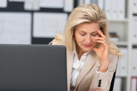 tired person: Middle-aged businesswoman suffering a stress headache sitting at her desk leaning her head on her hand with her eyes closed in pain
