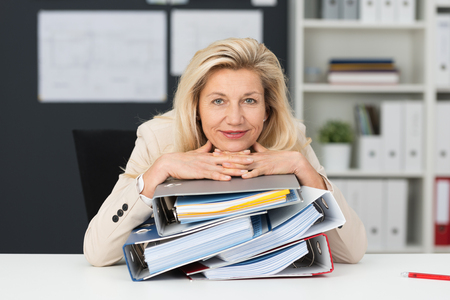Contented attractive blond middle-aged businesswoman sitting at her desk in the office leaning her head on a pile of office binders with a smile
