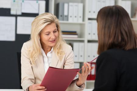 hoja de vida: Mujer oficial de personal haciendo una entrevista de trabajo con una candidata lectura a través de un archivo que contiene su CV