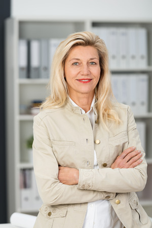 folded arms: Self-assured friendly attractive middle-aged businesswoman in a stylish jacket standing with folded arms smiling at the camera Stock Photo
