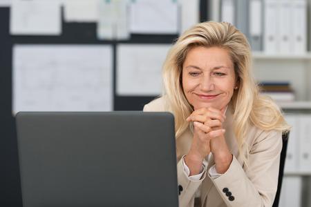 Freut attraktive Geschäftsfrau mittleren Alters sitzt an ihrem Schreibtisch mit einem breiten Lächeln Lesen von Informationen auf ihren Laptop-Bildschirm