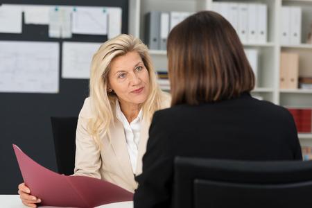 entrevista de trabajo: Atractivo elegante directora de mediana edad la realizaci�n de una entrevista de trabajo con un solicitante femenino que mira con curiosidad con su CV en la mano