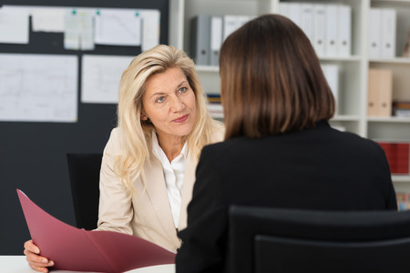 company employee: Attractive stylish middle-aged manageress conducting a job interview with a female applicant looking at her quizzically with her CV in her hand