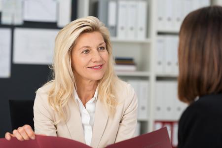 Geschäftsfrau ein Vorstellungsgespräch leiten Halten der weibliche Bewerber Lebenslauf in der Hand, als sie fragt sie im Büro Standard-Bild
