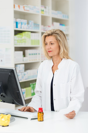 Attractive blond middle-aged female pharmacist checking stock on her computer as she stands at the counter in the pharmacy photo