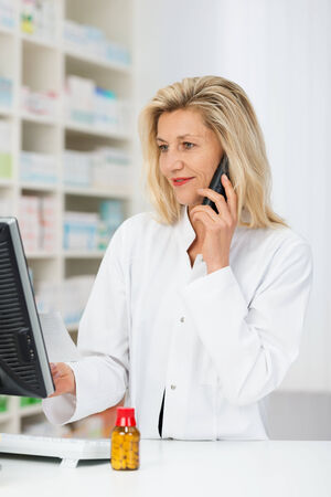 Helpful pharmacist chatting to a patient on the phone as she stands at her desk in the pharmacy checking information on her computer photo