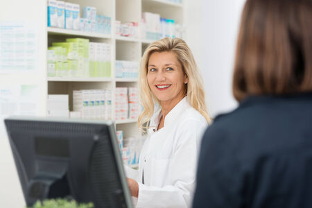 Attractive smiling female pharmacist assisting a patient in the pharmacy, over the shoulder view to the pharmacist photo