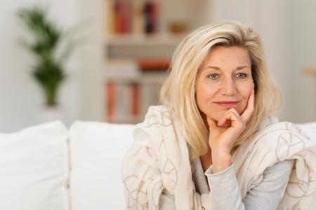 mujer pensativa: Mujer de mediana edad atractiva que se sienta en un sofá en casa soñando despierto apoyando la barbilla en la mano mirando hacia el lado con una expresión pensativa soñadora