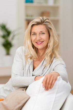 vejez feliz: Atractiva mujer de mediana edad confidente relajaba en su sofá mirando a la cámara con una sonrisa encantadora amistoso