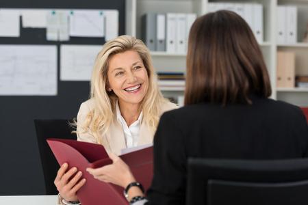 entrevista de trabajo: Directora atractiva la realización de una entrevista de trabajo con una candidata sonriéndole mientras discuten su CV Foto de archivo