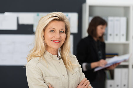 Confident attractive middle-aged businesswoman standing in her office with folded arms smiling at the camera as a colleague works in the background