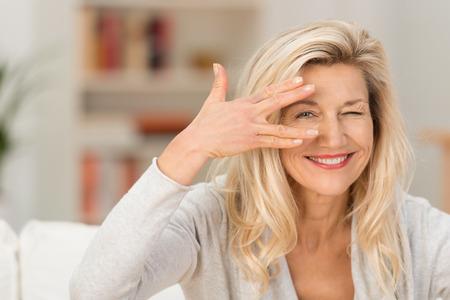 Leuke vrouw peering tussen haar vingers op de camera met een speelse glimlach als ze ontspant thuis in de woonkamer