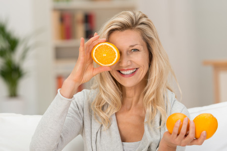 mid adults: Happy healthy woman playing with fresh ripe oranges holding two in her hand and a third halved fruit to her eye with a lovely smile