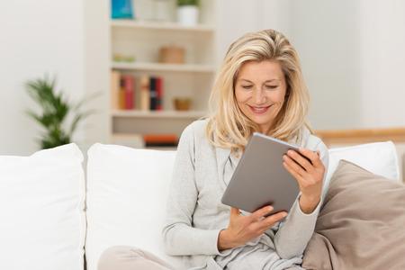 damas antiguas: Atractiva mujer de mediana edad rubia que lee un e-libro en su tableta relaja en un sof� en casa sonriendo mientras se disfruta de los contenidos Foto de archivo