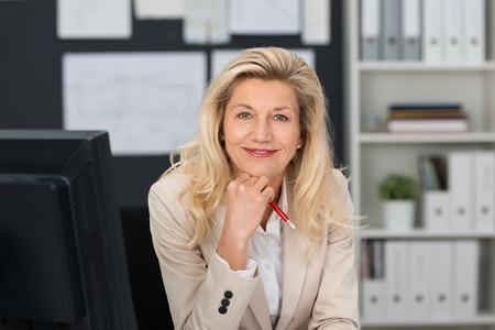 クローズ アップ、チンに片手でカメラに笑顔作業テーブルに座ってする中年金髪オフィスの女性
