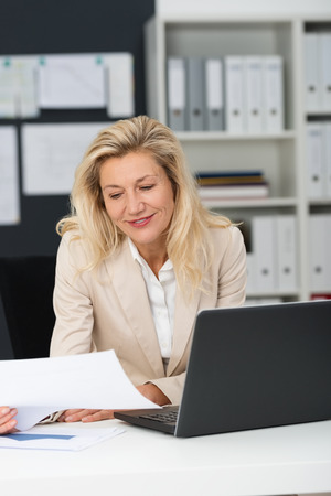 administration: Close up Smiling Adult Office Woman, with Blond Hair, Reading Document at her Office with Laptop on the Table.