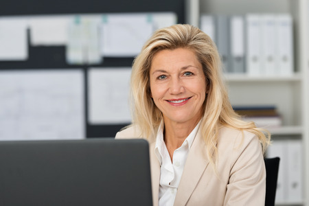 Close up Confident Adult Businesswoman, with Blond Hair, at her Office. Captured at her Working Table While Smiling at the Camera.