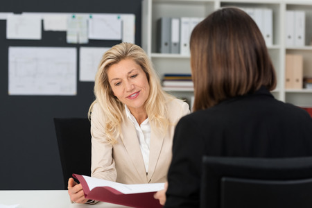 business matter: Close up Mature Businesswoman with Blond Hair Discussing Business Matter to her Assistant with Reference Document at her Office.