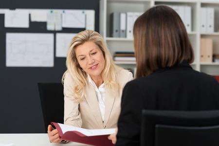 Close-up Oudere zakenvrouw met Blond Haar Bespreken Zaken Matter aan haar assistent met referentiedocument op haar kantoor. Stockfoto