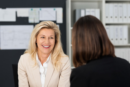 women talking: Close up Pretty Smiling Adult Manager Woman Talking to her Subordinate at her Office. Stock Photo
