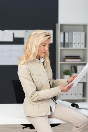 revisando documentos: Cierre de la empresaria madura con el pelo rubio que repasan documentos serio en la oficina mientras est� sentado en su mesa de trabajo Blanca.